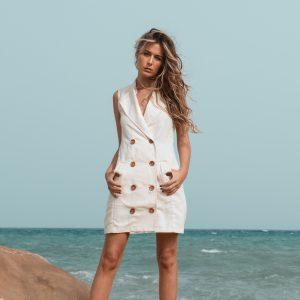 Vestido de lino cruzado con botones sin mangas color crudo modelo en la playa con vestido de lino de paloma lajud primavera verano 2021