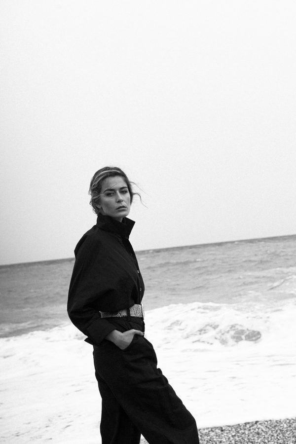 Camisa Miyako negra hecha de lino y algodon organico con mangas corte japones, puño vuelto y cuello con cuerpo para mantenerse alto, modelo con outfit negro y sombrero en la playa