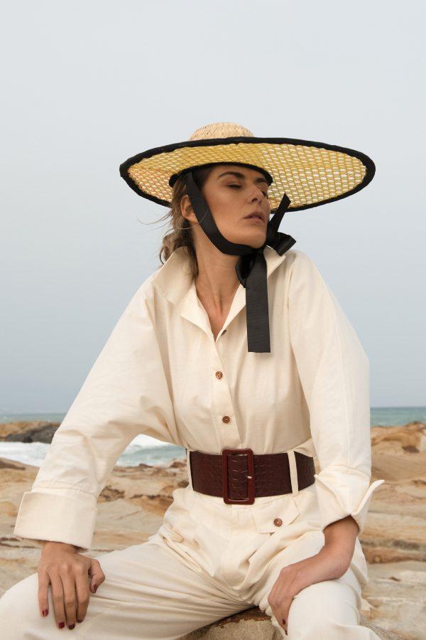 Camisa Miyako beige hecha algodon organico con mangas corte japones, puño vuelto y cuello con cuerpo para mantenerse alto, modelo con outfit negro y sombrero en la playa