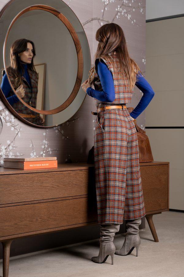 Chaleco de invierno corto, con hombreras, y detalles de botones dorados y un largo ideal para usar con pantalones de cintura alta, hecho de lana a cuadros estilo escocés azul y naranja.
