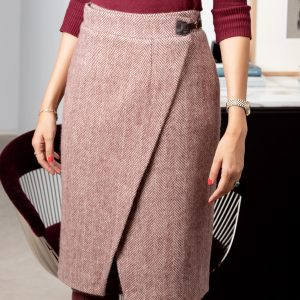 Falda cruzada con detalle de hebilla, con un largo ideal de bajo de la rodilla, forrada y hecha de lana con dibujo de espiga en tonos burdeos y crudo.