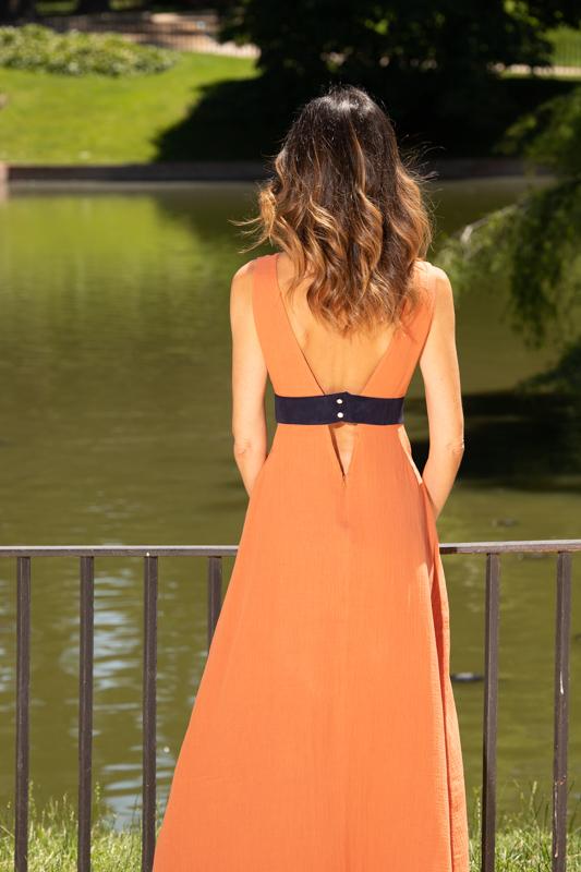 Vestido largo naranja escote V Roche con escote V, y como es verano no hemos dudado en hacer tres pequeños escotes mas de bajo de la banda a contraste color azul de ante italiano, en los costados y en la parte de atrás, que le dan un toque de originalidad y coqueteria sutil al que no te podrás resistir, ademas por su puesto de estar hecho de ALGODÓN ORGANICO, es un diseño cómodo, fresco, que no vas a querer quitarte todo el verano.
