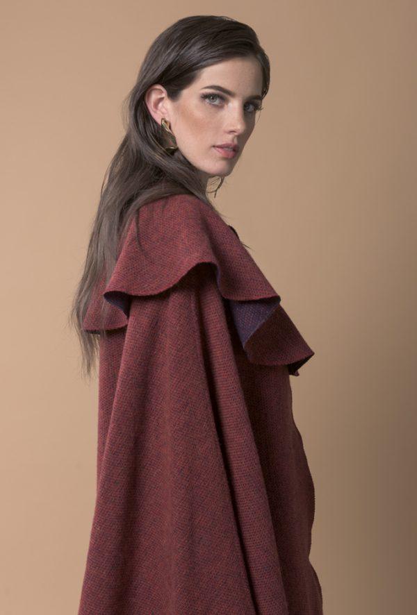 Capa de lana reversible, de corte clásico, esta hecho de lana 100% española, es ideal ya que tienes dos prendas en una al poder usarlo del lado en tono rojo y el otro lado en tono azul marino con tintes vino.